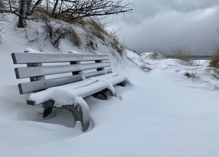 Snow covered bench along Lake Michigan